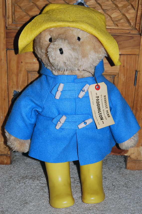 PADDINGTON BEAR. I used to own this same BEAR growing up. His yellow BOOTS and hat represent the sun, that brings out the (Jupiter) RAINbow when the rain washes away.